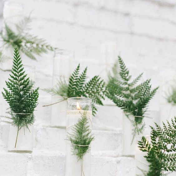 candles spruced up with ferns are a great idea to add a fresh touch to your minimalist Nordic wedding