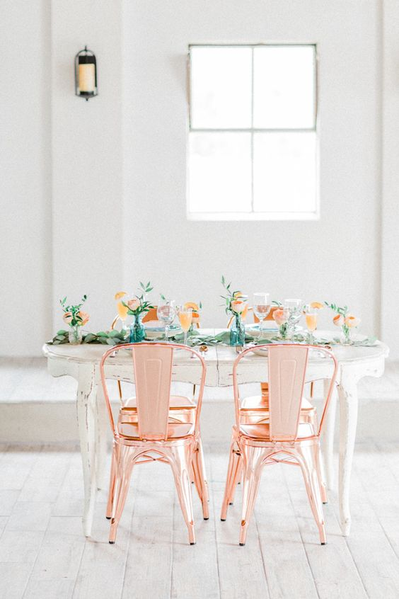copper chairs, a wedding reception table decorated with greenery and peachy blooms for a cool look