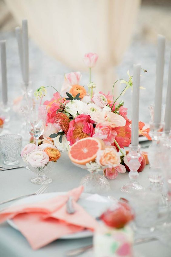 a beautiful wedding tablescape in dove grey and with orange, coral and hot pink details that make it bolder