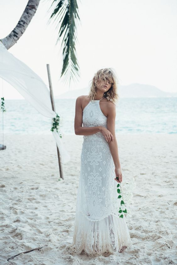 a boho lace wedding dress with a halter neckline and a lace skirt for a beach boho wedding