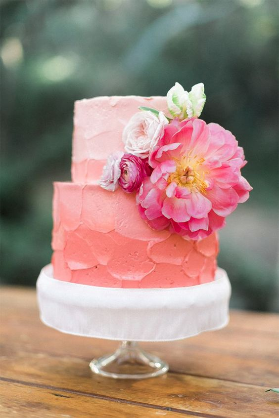 a buttercream ombre coral wedding cake with fresh blooms has a killing and very trendy look