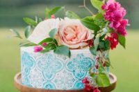21 a hand painted blue wedding cake topped with greenery, bright blooms and with azulejo tile patterns