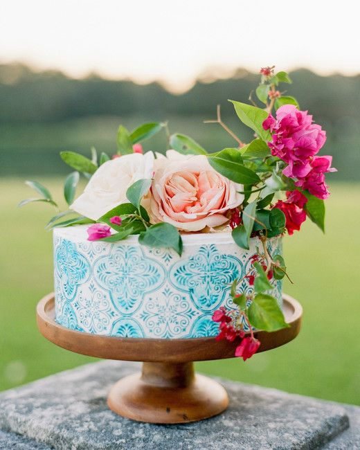 a hand painted blue wedding cake topped with greenery, bright blooms and with azulejo tile patterns