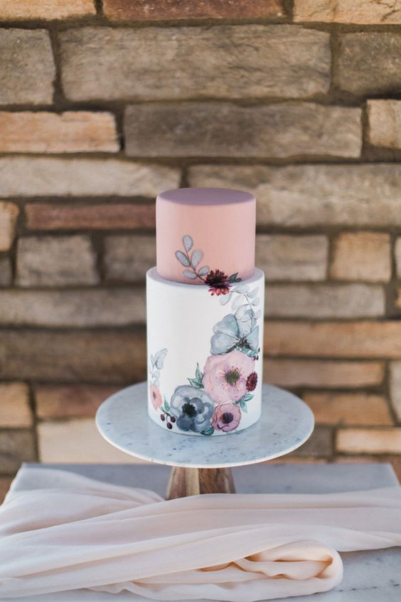 a chic and delicate wedding cake with a dusty pink upper tier and a white one with hand painted flowers on it
