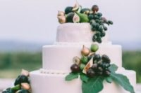 22 a large buttercream wedding cake topped with greenery, fresh grapes, pears and figs