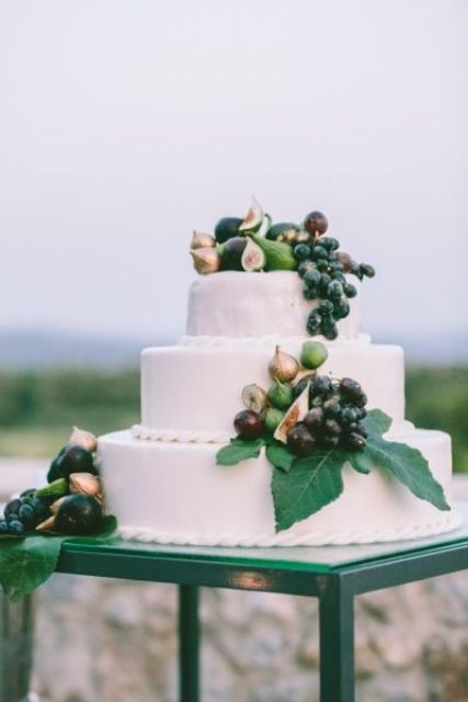 a large buttercream wedding cake topped with greenery, fresh grapes, pears and figs