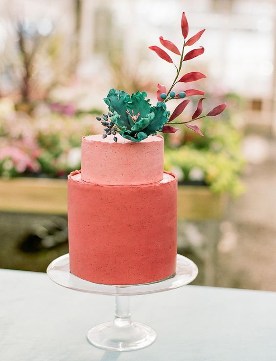 a mate coral wedding cake in two shades topped with a sugar bloom and foliage is a bright idea for any modern wedding