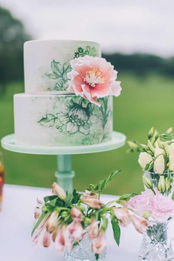 a chic handpainted wedding cake in green and white decorated with a single pink sugar bloom
