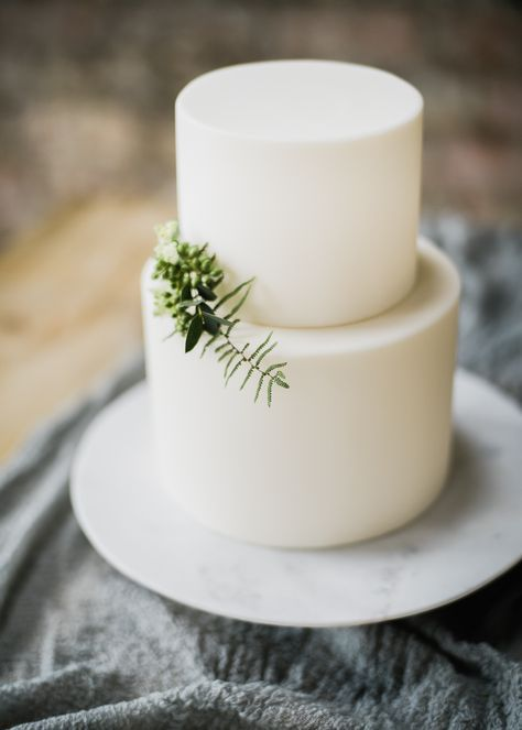 a minimalist plain white wedding cake topped with only a touch of greenery is a beautiful idea with no fuss