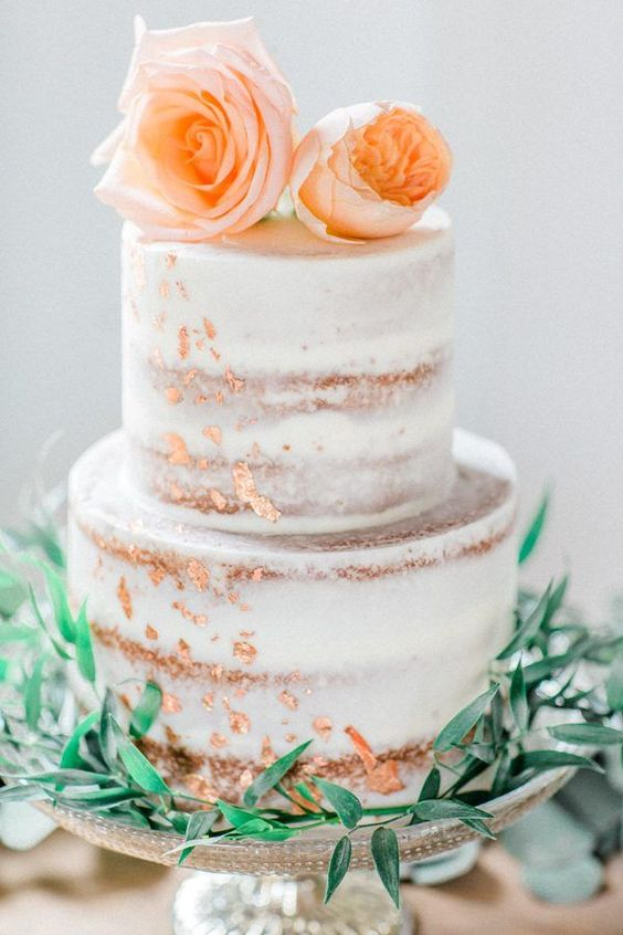 a naked wedding cake with peahcy blooms on top and copper leaf decor is an gorgeous and trendy idea