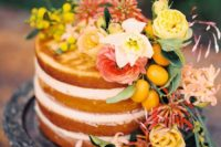 23 a naked wedidng cake decorated with bright florals, greneery and kumquats