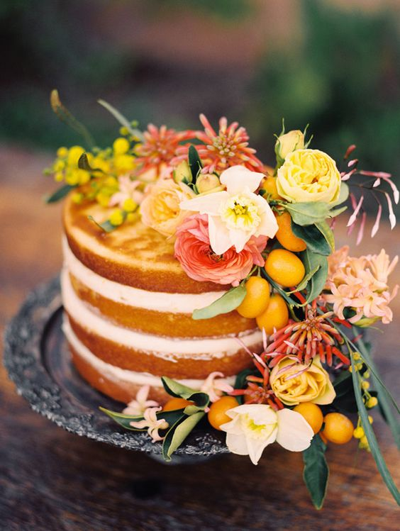 a naked wedidng cake decorated with bright florals, greneery and kumquats