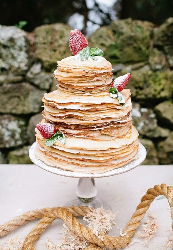 a crepe wedding cake topped with strawberries is another good idea for brunch weddings