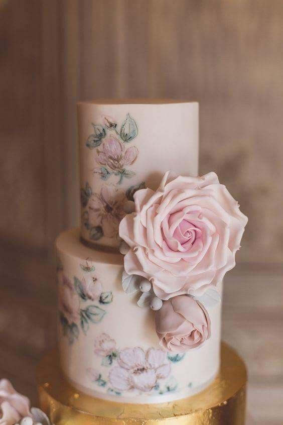 a delicate wedding cake with pastel handpainted blooms and very natural looking pastel sugar blooms