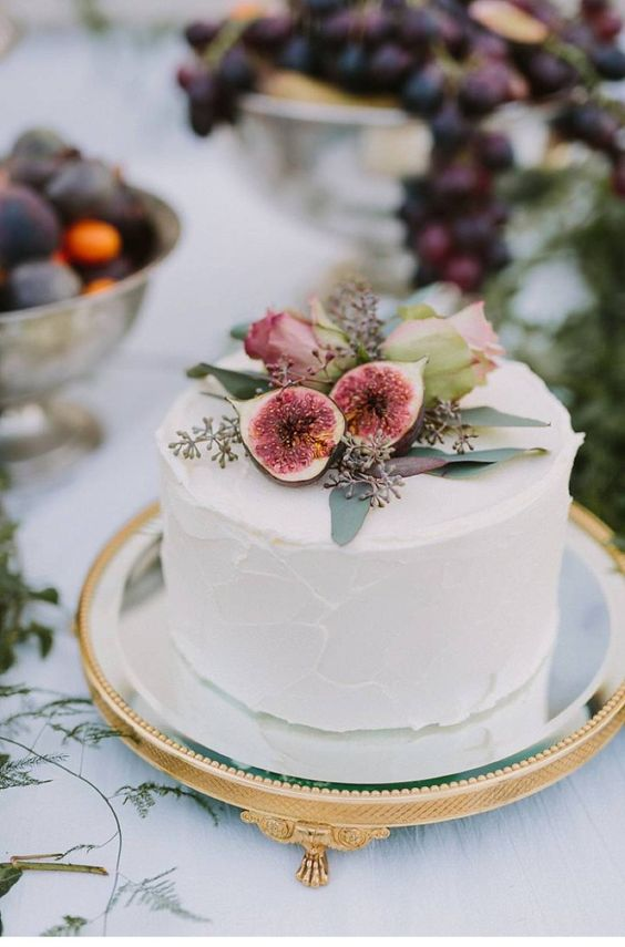 a simple buttercream wedding cake topped with figs and fresh blooms is amazing for a Mediterranean wedding