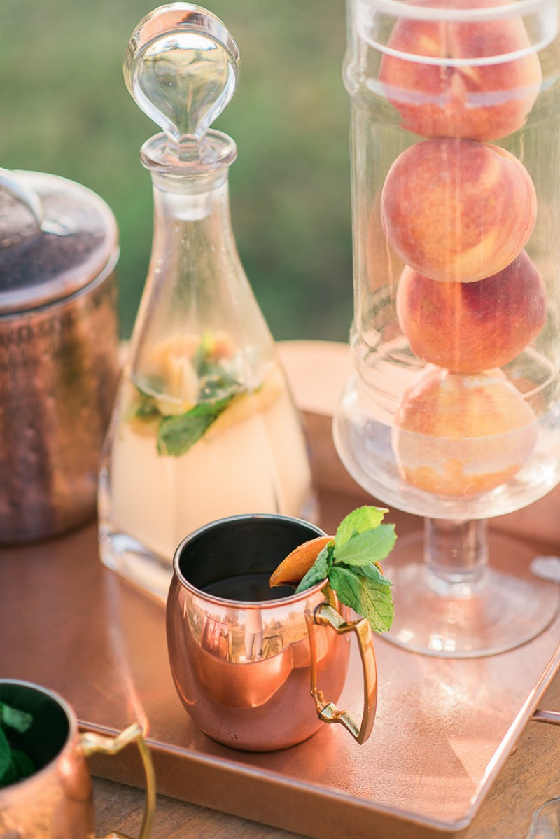 a stylish wedding bar with copper mugs, trays and jars and real peaches in a tall glass vase to add them to drinks