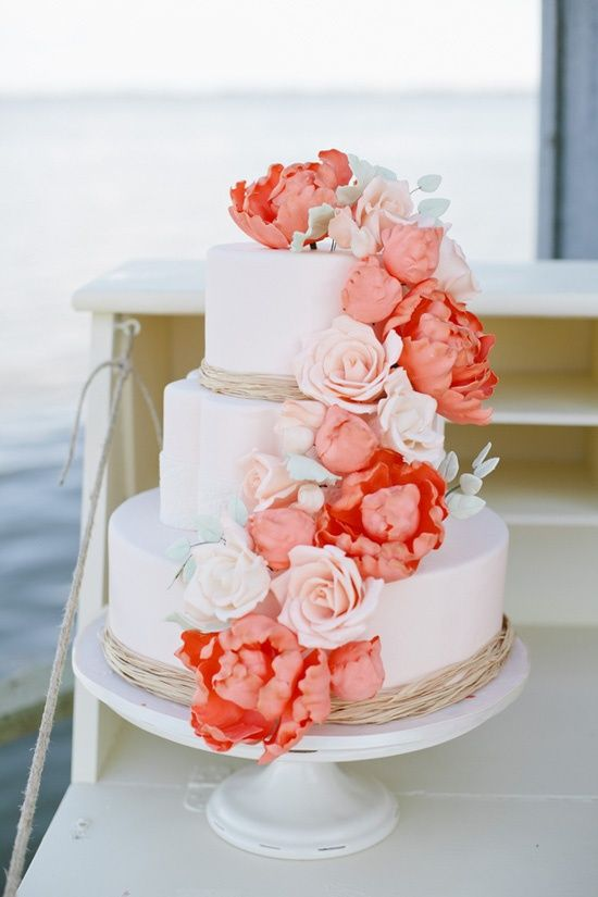 a wedding cake decorated with white and coral sugar flowers is a great idea to add colorful touch to the dessert table