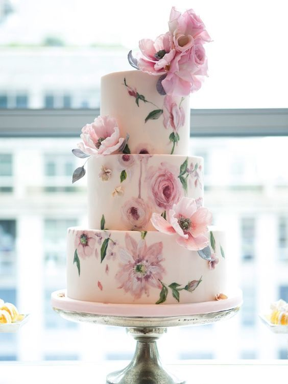 a tender pastel handpainted floral wedding cake done in pinks and greens and decorated with natural blooms