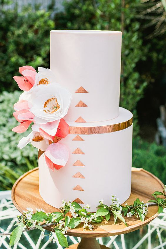 a white wedding cake decorated with copper leaf, with white and coral blooms on a wooden stand