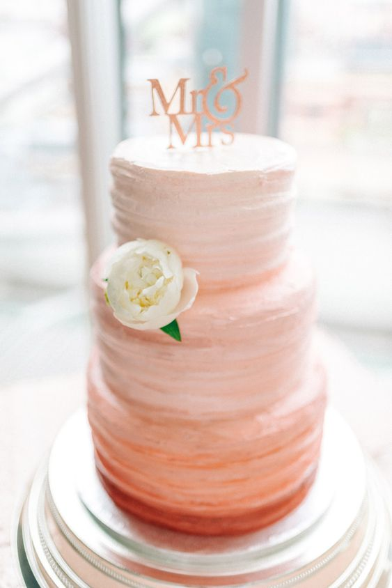 an ombre coral wedding cake with a pink letter topper and a single fresh bloom for a subtle color touch
