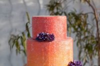 26 a unique gradient coral to yellow wedding cake topped with purple sugar flowers for a bold wedding