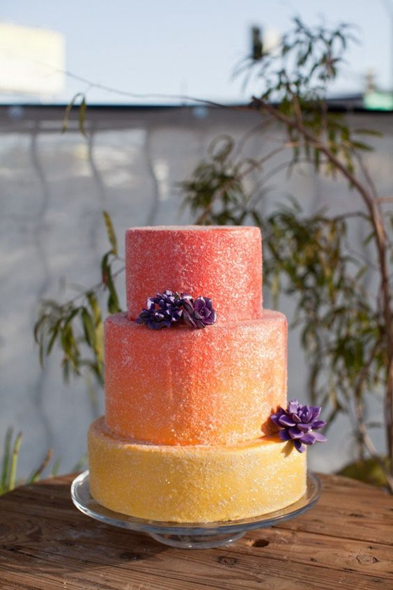 a unique gradient coral to yellow wedding cake topped with purple sugar flowers for a bold wedding