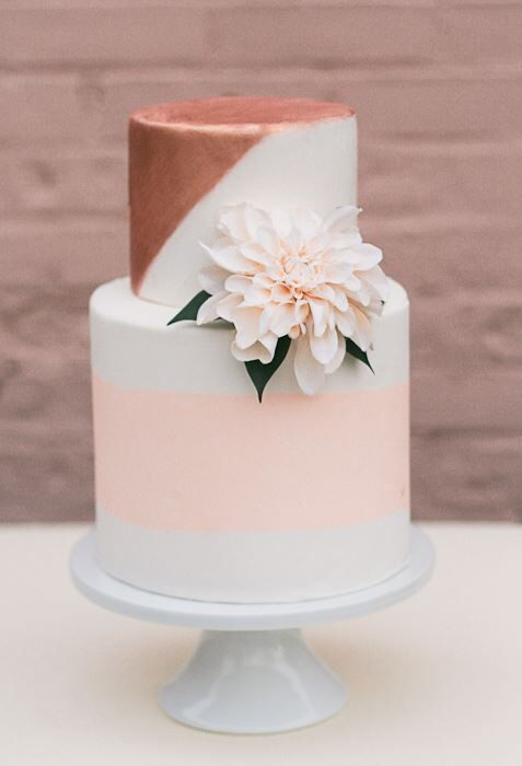 a white wedding cake with a peachy pink stripe and copper geometric decor plus a blush bloom
