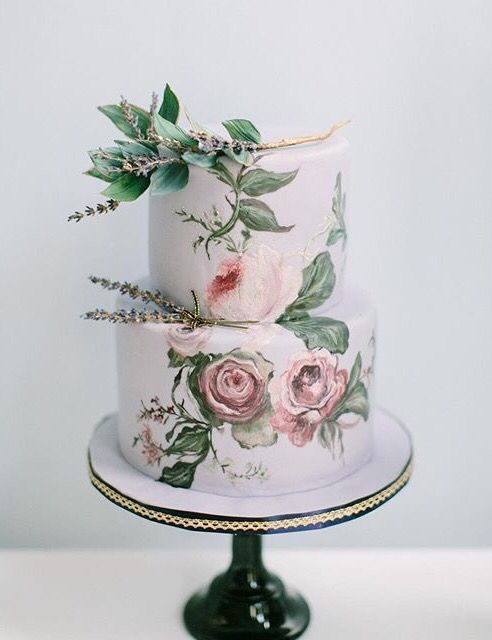 an exquisite handpainted wedding cake with rose and some lavender on top looks like a real work of art