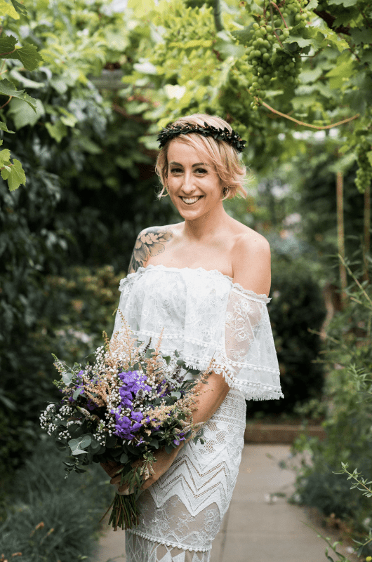 The bride was wearing a boho lace off the shoulder mermaid wedding dress and a greenery crown