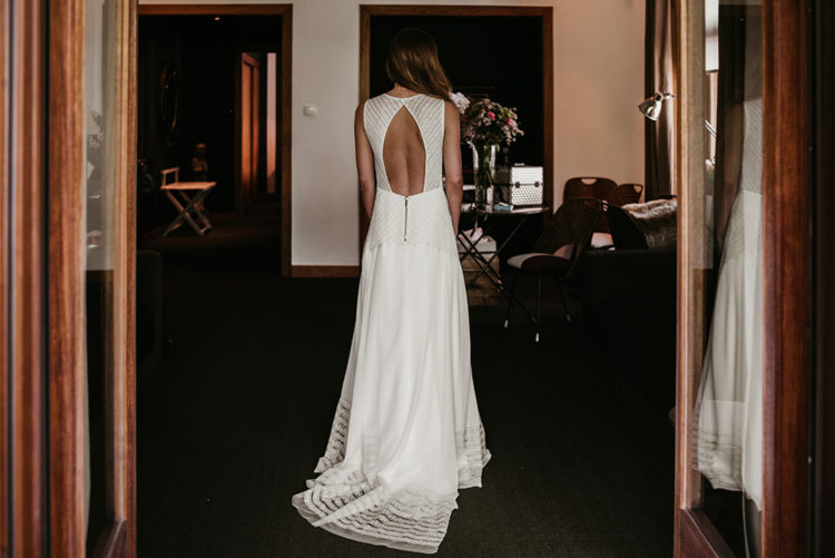 The bride was wearing a chic sleeveless A-line wedding dress with a cutotu back, a touch of sparkle and a train