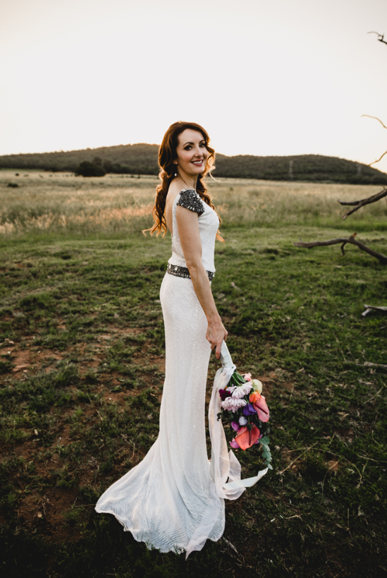 The bride was wearing a fully embellished fitting wedding gown with a cutout back, grey embellished shoulders and a sash