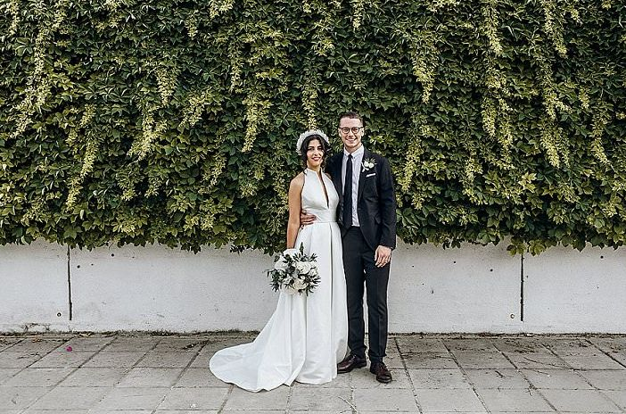The bride was wearing a plain A-line wedding gown with an accented waist and a plunging neckline