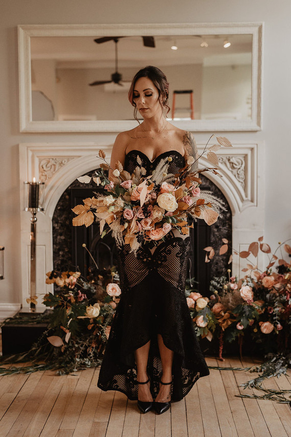 The bride was wearing a strapless black and blush midi gown with a high low skirt