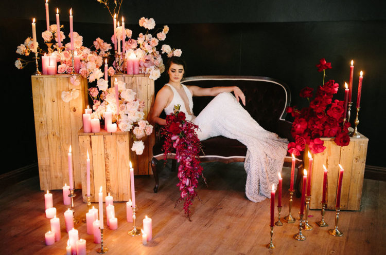 The wedding lounge was styled with pink and red blooms and lots of candles plus a velvet coach