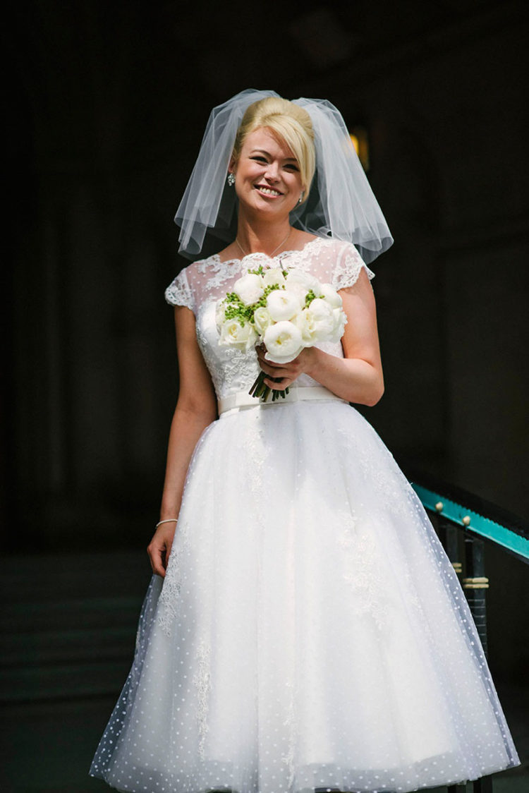 a 50s inspired bridal look with a polka dot sleeveless tea-length wedding dress with a sash, statement earrings and a veil
