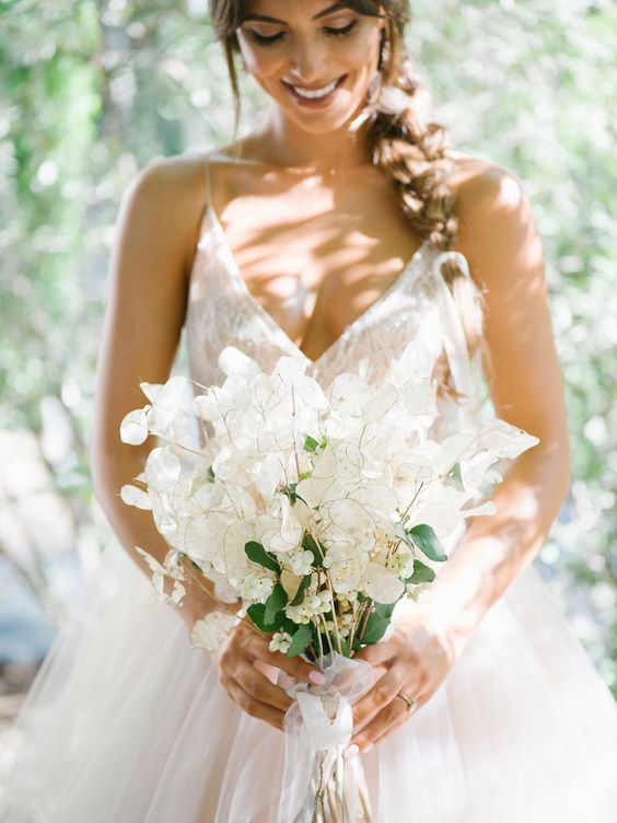 a chic and ethereal lunaria wedding bouquet with some berries and neutral ribbons for a spring bride
