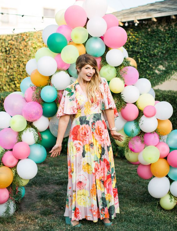 a colorful triangle-shaped balloon and greenery wedding arch for a whimsical wedding