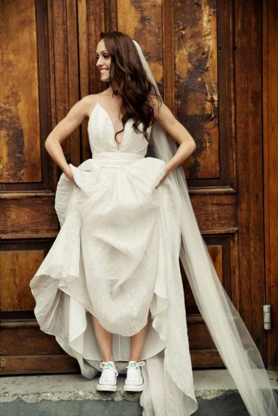 a modern bridal look with a spaghetti strap A-line wedding dress, a long veil and white Converse for a touch of fun