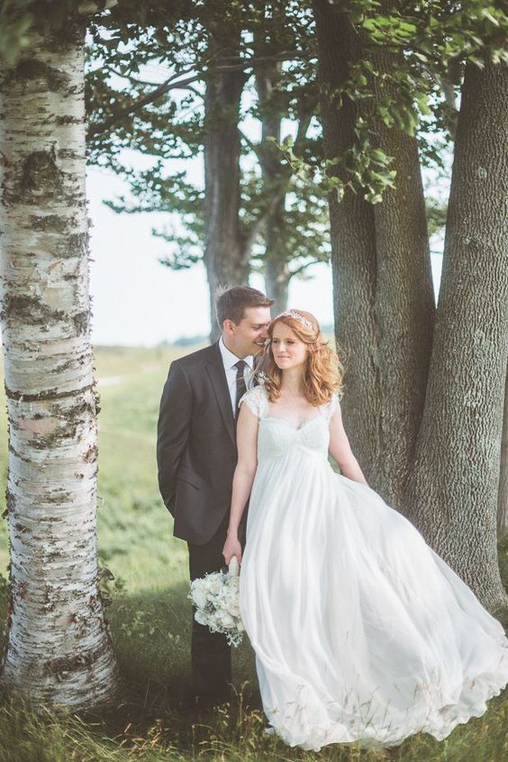 a romantic and vintage-inspired empire waist wedding dress with a lace bodice, cap sleeves and a plain flowy skirt