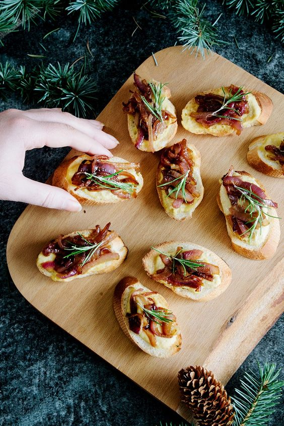 hummus and caramelized onion crostini with soem rosemary on top are a delicious idea