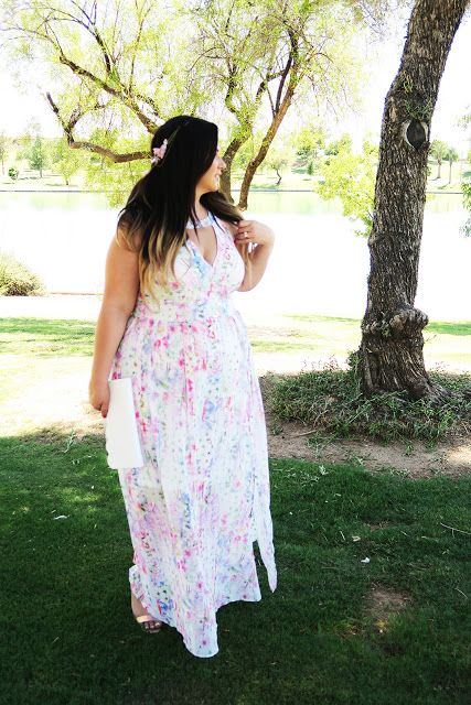 a beautiful bright floral print maxi dress with a V-neckline, no sleeves, a white clutch and pink shoes for a summer wedding
