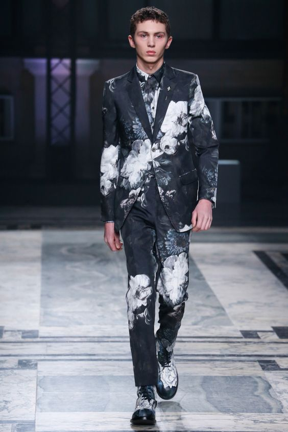 a black suit and shirt with a realistic floral print in white and matching shoes for a moody groom's look