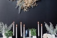03 a black wall accented with an oversized lunaria decoration with pale miller, it looks very wintry-like