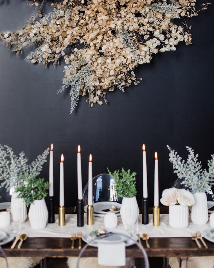 a black wall accented with an oversized lunaria decoration with pale miller, it looks very wintry-like