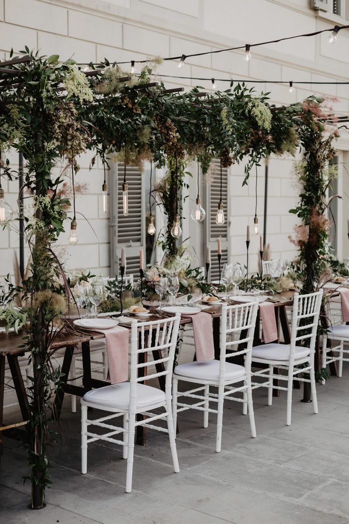 a bold floral and greenery overhead decoration is a fresh alternative to usual on table wedding decor