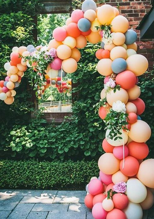 a colorful balloon wedding arch with pink and neutral blooms and greenery for a modern wedding