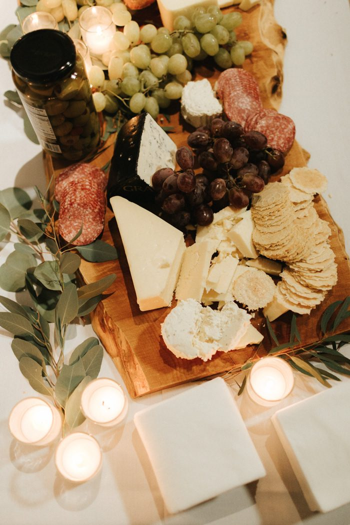 a deliciously styled charcuterie board with various cheese, salami, grapes and decorated with candles and greenery
