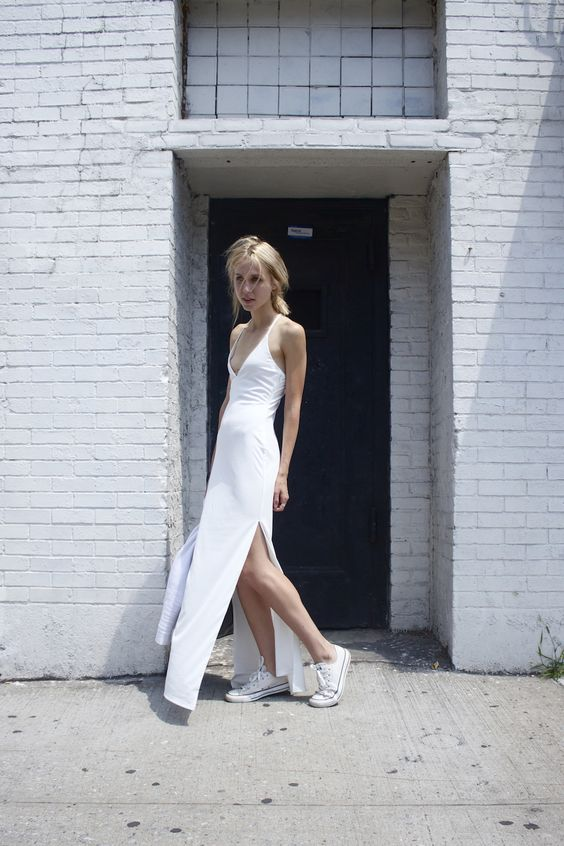 a minimalist bridal look with a plain fitting dress with a plunging neckline, side slits and white Converse