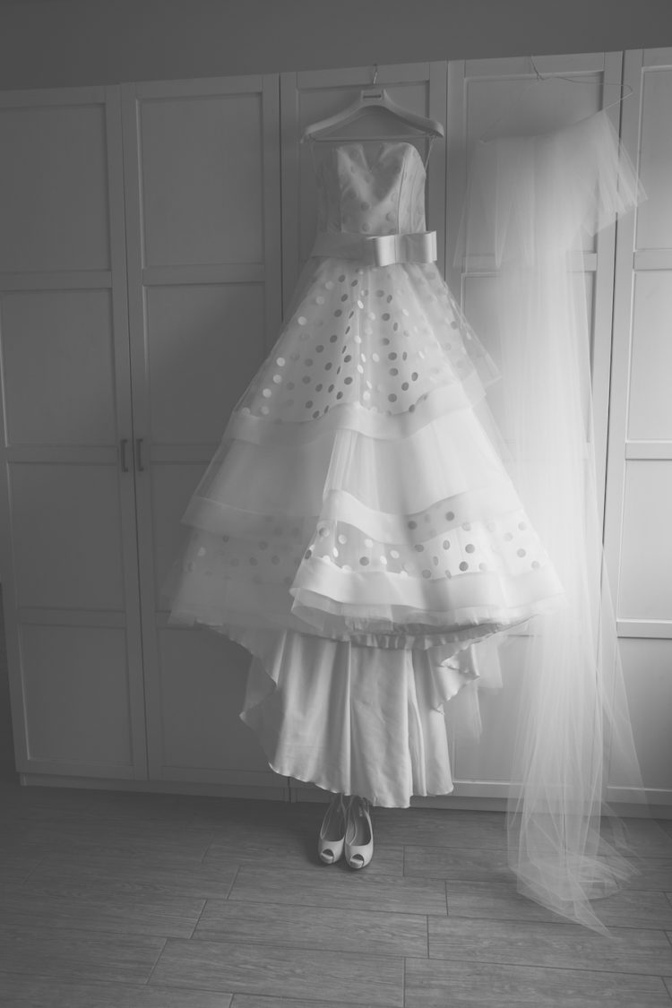 a retro-inspired A-line polka dot wedding dress with a train, a large bow sash and a long veil