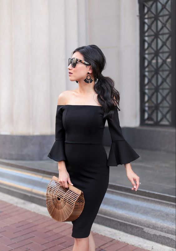 an off the shoulder black knee dress with bell sleeves is a modern take on a traditional little black dress, statement earrings and a wooden bag